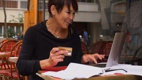 Ο σε αργή κίνηση θηλυκός πελάτης του ομο-εργαζόμενου κέντρου κάνει τις αγορές από την πιστωτική κάρτα σε Διαδίκτυο με το lap-top φιλμ μικρού μήκους