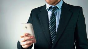 Ο σε αργή κίνηση, κομψός επιχειρηματίας χρησιμοποιεί ένα κινητό τηλέφωνο τυπώνει sms ή ηλεκτρονικό ταχυδρομείο απόθεμα βίντεο
