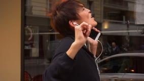 Ο σε αργή κίνηση μέσης ηλικίας θηλυκός τουρίστας ακούει μουσική με το smartphone και το χορό απόθεμα βίντεο