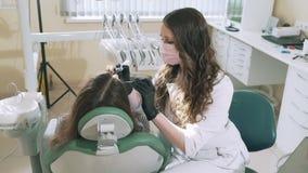 Ο σε αργή κίνηση οδοντίατρος γιατρών πυροβολισμού κινηματογραφήσεων σε πρώτο πλάνο steadicam χρησιμοποιεί ένα οδοντικό τρυπάνι κα απόθεμα βίντεο