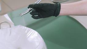 Ο σε αργή κίνηση οδοντίατρος γιατρών πυροβολισμού κινηματογραφήσεων σε πρώτο πλάνο στα αποστειρωμένα γάντια ελέγχει την εργασία τ απόθεμα βίντεο