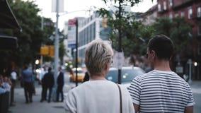 Ο σε αργή κίνηση πίσω ειρηνικοί άνδρας και η γυναίκα άποψης περπατούν μαζί να κρατήσουν τα χέρια απολαμβάνοντας τα αστικά τοπία β φιλμ μικρού μήκους