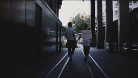 Ο σε αργή κίνηση πίσω unrecognizable άνδρας και η γυναίκα άποψης περπατούν μαζί να κρατήσουν τα χέρια στις ράγες κάτω από τη μεγά φιλμ μικρού μήκους