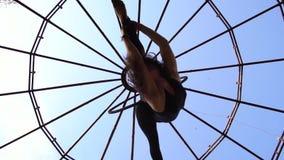 Ο σε αργή κίνηση πυροβολισμός, το brunette κάνει έναν σπάγγο και τις στροφές σε ένα δαχτυλίδι για το εναέριο acrobatics φιλμ μικρού μήκους