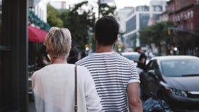 Ο σε αργή κίνηση unrecognizable άνδρας και η γυναίκα περπατούν τα χέρια εκμετάλλευσης γύρω από τις οδούς βραδιού της πίσω άποψης  απόθεμα βίντεο