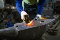 Ο σιδηρουργός σφυρηλατεί το φωτεινό μέταλλο στο φούρνο, κλωτσά έξω τους σπινθήρες στοκ εικόνα
