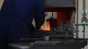 Ο σιδηρουργός παίρνει έξω το μέρος χάλυβα από το φούρνο σφυρηλατήστε απόθεμα βίντεο