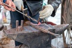 Ο σιδηρουργός σφυρηλατεί ένα καυτό πέταλο στο αμόνι Στοκ Εικόνες