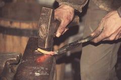 Ο σιδηρουργός σφυρηλατεί ένα red-hot σφυρί μετάλλων Στοκ Εικόνα