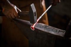Ο σιδηρουργός σφυρηλατεί το καυτό μέταλλο Στοκ φωτογραφία με δικαίωμα ελεύθερης χρήσης