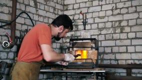 Ο σιδηρουργός τοποθετεί το στοιχείο στο φούρνο φιλμ μικρού μήκους