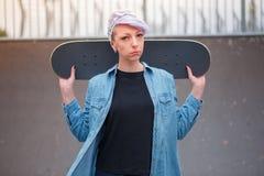 Ο σκέιτερ κοριτσιών κρατά skateboard πίσω από την πίσω Στοκ Εικόνες