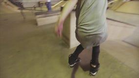 Ο σκέιτερ κυλίνδρων στο καπέλο κάνει το ακραίους πίσω κτύπημα και το γύρο στην άκρη της αφετηρίας στο skatepark πρόκληση απόθεμα βίντεο