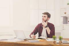 Ο σκεπτικός νέος επιχειρηματίας παίρνει τις σημειώσεις στο σύγχρονο άσπρο γραφείο στοκ φωτογραφία με δικαίωμα ελεύθερης χρήσης