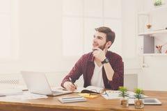 Ο σκεπτικός νέος επιχειρηματίας παίρνει τις σημειώσεις στο σύγχρονο άσπρο γραφείο στοκ εικόνες με δικαίωμα ελεύθερης χρήσης