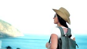 Ο σκεπτικός νέος ταξιδιώτης γυναικών στα γυαλιά ηλίου και το καπέλο που συλλογίζεται την όμορφη seascape πλάτη βλέπουν απόθεμα βίντεο