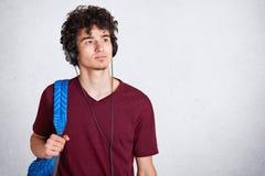 Ο σκεπτικός νέος τύπος με τα ακουστικά στο επικεφαλής και μπλε σακίδιο, που φορά την καφέ περιστασιακή μπλούζα, ακούει τη μουσική στοκ φωτογραφία με δικαίωμα ελεύθερης χρήσης