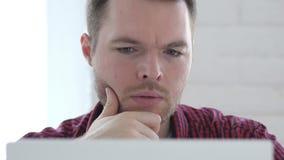 Ο σκεπτικός νεαρός άνδρας που σκέφτεται και που εργάζεται στο lap-top, αντιμετωπίζει κοντά επάνω φιλμ μικρού μήκους