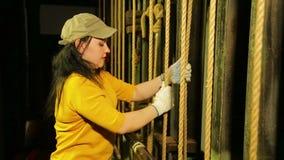 Ο σκηνικός εργαζόμενος θηλυκών στα γάντια ανυψώνει την κουρτίνα θεάτρων και στερεώνει το καλώδιο απόθεμα βίντεο