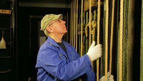 Ο σκηνικός εργαζόμενος στα γάντια αφαιρεί το υποστήριγμα από το καλώδιο του ανυψωτικού μηχανισμού της κουρτίνας θεάτρων και χαμηλ απόθεμα βίντεο