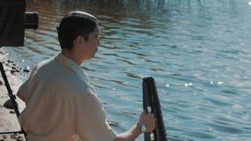 Ο σκηνοθέτης στην τρίχα καθαρή φωνάζει στον ομιλητή τρώει τα σταφύλια στην ακτή λιμνών με τη κάμερα απόθεμα βίντεο