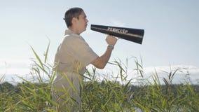 Ο σκηνοθέτης στον καθαρό κάλαμο στάσεων τρίχας έξω στην ακτή λιμνών και φωνάζει στον ομιλητή απόθεμα βίντεο