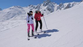 Ο σκιέρ γυναικών στέκεται στην κλίση σκι βουνών, κοντά στα φρένα της ο φίλος της και χαιρετά απόθεμα βίντεο