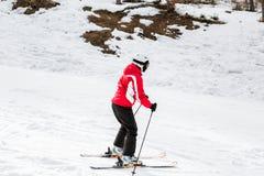 Ο σκιέρ κάνει σκι κάτω από την κλίση στα ξύλα Στοκ Φωτογραφία