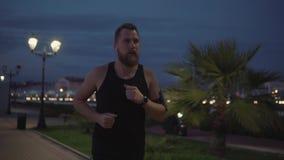 Ο σκληραγωγημένος αρσενικός αθλητικός τύπος μόνο στη νύχτα, κοιτάζοντας στο ρολόι απόθεμα βίντεο