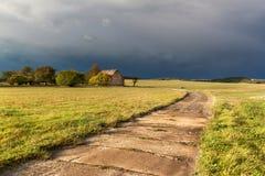 Ο σκοτεινός ουρανός πριν από τη θύελλα σιταποθήκη παλαιά Βράδυ φθινοπώρου με τα μαύρα σύννεφα Στοκ Φωτογραφία