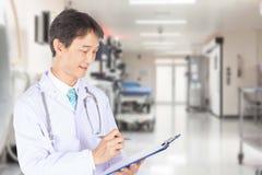 Ο σοβαρός αρσενικός γιατρός διαβάζει τις πληροφορίες ασθενών Στοκ φωτογραφία με δικαίωμα ελεύθερης χρήσης