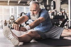 Ο σοβαρός γενειοφόρος ηληκιωμένος απολαμβάνει τις ασκήσεις στο κέντρο ικανότητας Στοκ φωτογραφίες με δικαίωμα ελεύθερης χρήσης