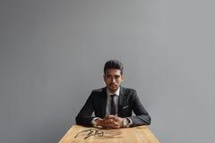 Ο σοβαρός επιχειρηματίας κάθεται στο γραφείο και εξετάζει τη κάμερα Στοκ Εικόνα