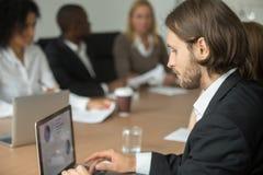 Ο σοβαρός επιχειρηματίας που εργάζεται στο lap-top on-line σε διαφορετικό με ομαδοποιεί Στοκ Εικόνα