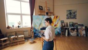 Ο σοβαρός καλλιτέχνης εργάζεται στο εργαστήριο που στέκεται μπροστά από easel με τη βάρκα εικόνων παλετών και βουρτσών και ζωγραφ φιλμ μικρού μήκους