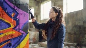 Ο σοβαρός νέος καλλιτέχνης γκράφιτι γυναικών χρωματίζει στη στήλη στην παλαιά αποθήκη εμπορευμάτων χρησιμοποιώντας το χρώμα ψεκασ φιλμ μικρού μήκους