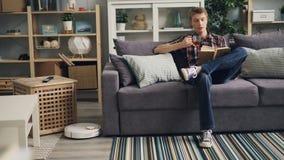 Ο σοβαρός νεαρός άνδρας πίνει το τσάι και διαβάζει τη συνεδρίαση βιβλίων στον καναπέ στο ελαφρύ επίπεδο ενώ η ρομποτική ηλεκτρική απόθεμα βίντεο