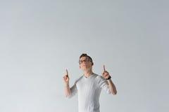 Ο σοβαρός νεαρός άνδρας δείχνει τους δείκτες του επάνω Στοκ Φωτογραφία