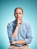 Ο σοβαρός νεαρός άνδρας πέρα από το μπλε υπόβαθρο Στοκ φωτογραφίες με δικαίωμα ελεύθερης χρήσης