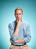 Ο σοβαρός νεαρός άνδρας πέρα από το μπλε υπόβαθρο Στοκ Φωτογραφία