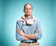 Ο σοβαρός νεαρός άνδρας πέρα από το μπλε υπόβαθρο Στοκ Εικόνες