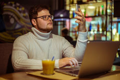 Ο σοβαρός νεαρός άνδρας που εργάζεται στο lap-top στον καφέ Στοκ Εικόνες