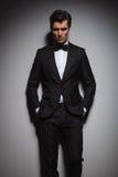 Ο σοβαρός νεαρός άνδρας που φορά το σμόκιν που στέκεται με παραδίδει τις τσέπες Στοκ Εικόνες