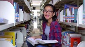 Ο σπουδαστής διαβάζει το βιβλίο στο διάδρομο και το χαμόγελο βιβλιοθηκών απόθεμα βίντεο