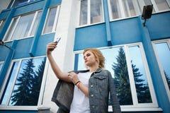 Ο σπουδαστής κάνει ένα μόνος-πορτρέτο με ένα smartphone, όμορφο κορίτσι hipster παίρνοντας τις εικόνες τους με έναν κινητό στοκ φωτογραφία