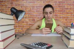Ο σπουδαστής, κορίτσι γράφει στο σημειωματάριο μεταξύ των βιβλίων Κορίτσι που εργάζεται στην εργασία του νέο ελκυστικό κορίτσι σπ Στοκ Εικόνα
