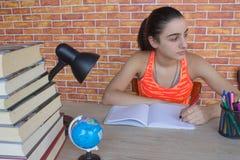 Ο σπουδαστής, κορίτσι γράφει στο σημειωματάριο μεταξύ των βιβλίων Κορίτσι που εργάζεται στην εργασία του νέο ελκυστικό κορίτσι σπ Στοκ Εικόνες