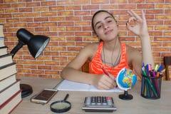 Ο σπουδαστής, κορίτσι γράφει στο σημειωματάριο μεταξύ των βιβλίων Κορίτσι που εργάζεται στην εργασία του νέο ελκυστικό κορίτσι σπ Στοκ εικόνες με δικαίωμα ελεύθερης χρήσης
