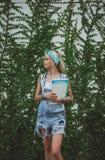 Ο σπουδαστής υπερασπίζεται τον τοίχο με τις πράσινες εγκαταστάσεις περιμένοντας τις κατηγορίες στη βιολογία κορίτσι σύγχρονο Πρότ στοκ φωτογραφία με δικαίωμα ελεύθερης χρήσης