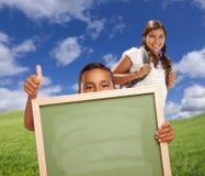 Ο σπουδαστής αγοριών δίνει τους αντίχειρες επάνω στον κενό πίνακα κιμωλίας εκμετάλλευσης Στοκ Φωτογραφία